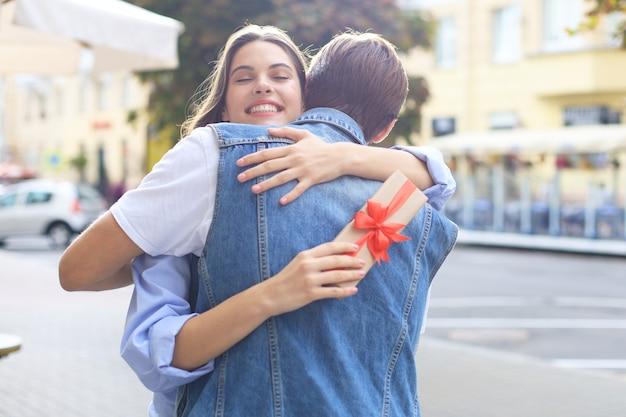 Immagine di una donna attraente con scatola regalo che abbraccia il suo uomo.