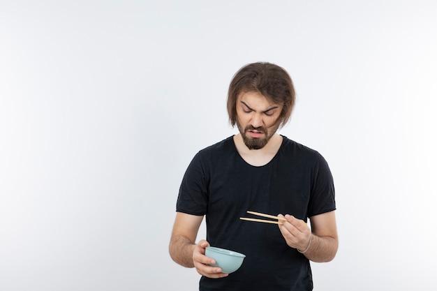 Immagine dell'uomo barbuto che tiene la ciotola con le bacchette su un muro bianco.