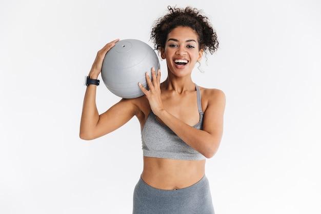 Immagine di una bellissima giovane donna africana di fitness sportivo incredibile in posa isolata sul muro bianco con la palla.