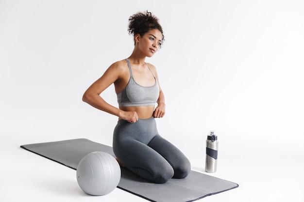 Immagine di una bellissima giovane donna africana di fitness sportivo stupefacente in posa isolata sul muro bianco.