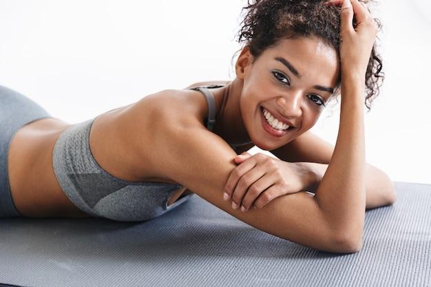 L'immagine di una bellissima giovane donna africana di fitness sportivo più forte fa esercizi isolati sul muro bianco.