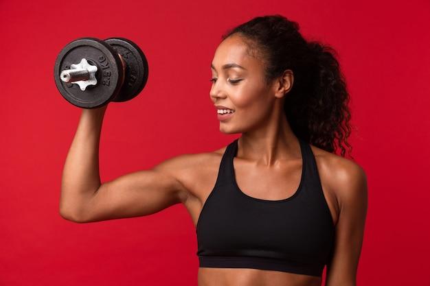 Immagine di bella donna afroamericana in abiti sportivi neri sollevamento manubri, isolato sopra la parete rossa