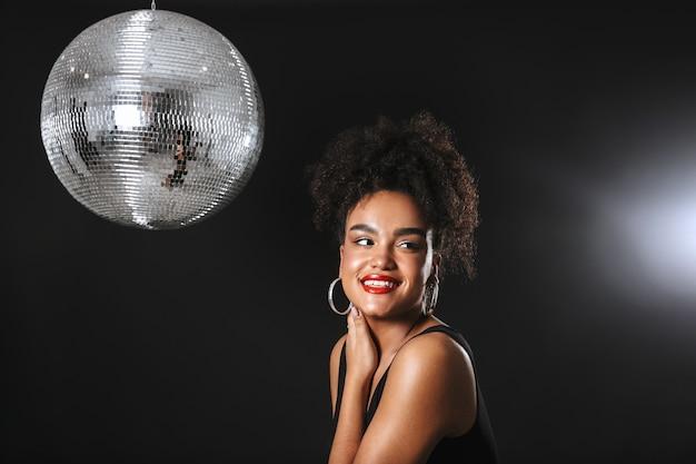 Immagine di bella donna africana in piedi con la palla da discoteca d'argento