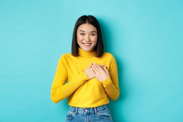 Immagine di bella donna asiatica che tiene le mani sul cuore e sorridente, ringraziandoti, sentendosi grato, in piedi su sfondo blu