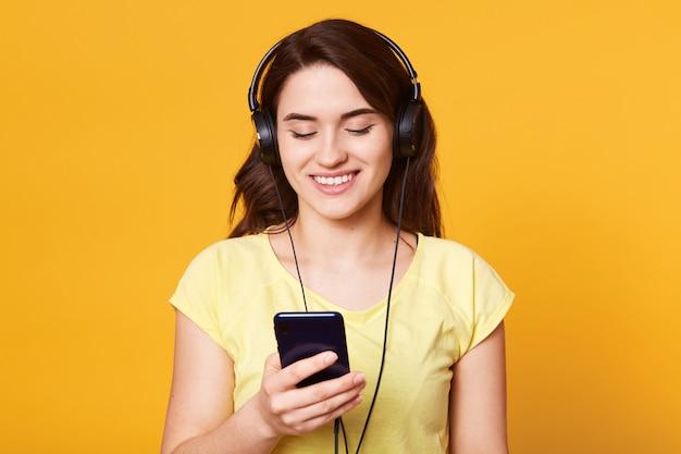 L'immagine della bella ragazza mora in camicia casual si rilassa con la musica preferita.