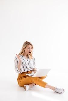 Immagine di bella donna eccitata che indossa abiti casual guardando il laptop mentre era seduto sul pavimento isolato sopra il muro bianco