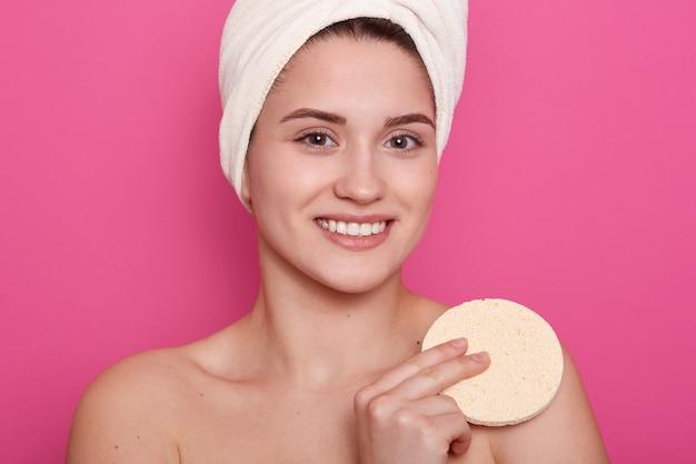 L'immagine di una bella ragazza con un asciugamano bianco in testa, sta sorridendo e tenendo in mano una spugna