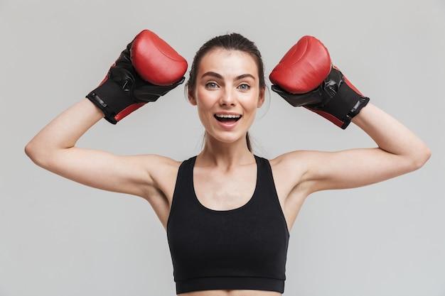 L'immagine di un pugile di una bella donna felice eccitata giovane sport fitness isolato sul muro grigio fa esercizi con i guanti.