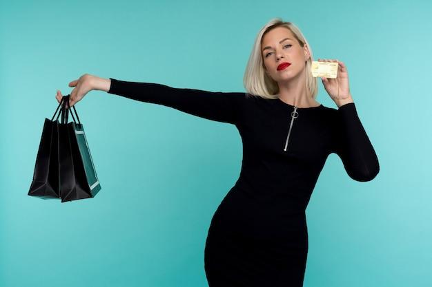 Immagine di bella giovane donna bionda felice che posa sopra i sacchetti della spesa della tenuta della parete blu.