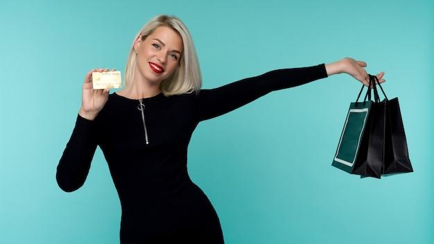 Immagine di una bella giovane donna bionda felice in posa isolato su sfondo blu muro tenendo le borse della spesa. concetto di vacanza del black friday. vendita