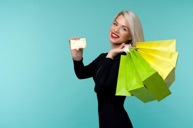 Immagine di una bella giovane donna bionda felice in posa isolata sopra lo spazio della parete blu che tiene i sacchetti della spesa. concetto di vacanza del black friday. vendita
