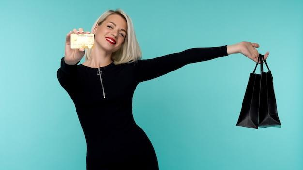 Immagine di una bella giovane donna bionda felice in posa isolata sopra la parete blu