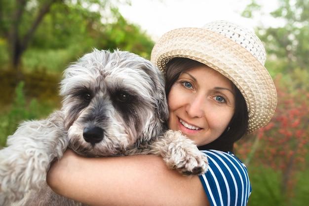 Immagine di bella donna di mezza età che indossa il cappello di paglia che osserva da parte mentre si cammina nel parco estivo