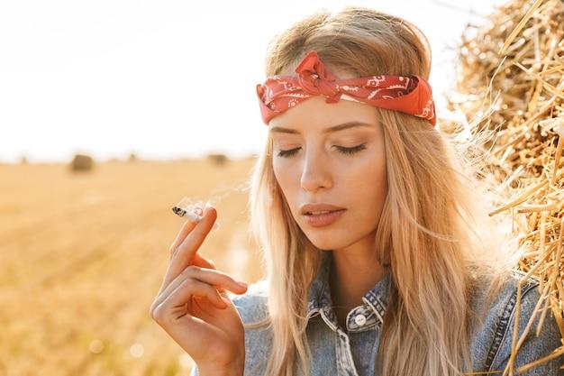 Immagine di bella donna 20s in piedi vicino a un grande pagliaio in campo dorato e fumo di sigaretta durante la giornata di sole