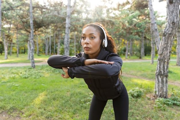 Immagine di bella donna 20s che indossa tuta nera che lavora e che allunga il corpo nel parco verde