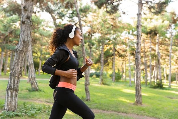 Immagine di una bella donna 20s che indossa una tuta nera che lavora fuori, mentre correva attraverso il parco verde