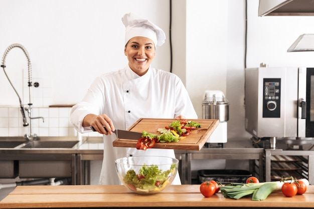 Immagine della bella donna capo che indossa l'uniforme bianca che produce insalata con verdure fresche, in cucina al ristorante
