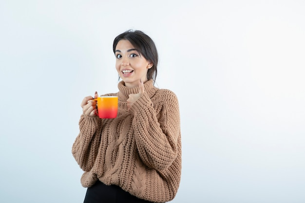 Immagine di bella donna in maglieria che tiene tazza di tè arancione