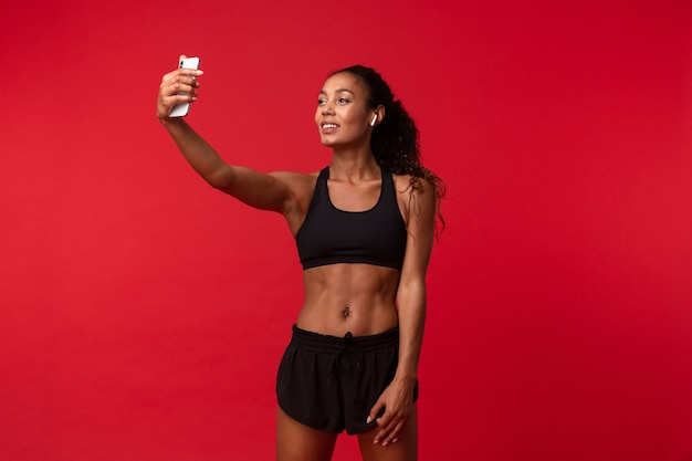 L'immagine di una bella giovane donna africana di forma fisica di sport che posa isolata sopra la musica d'ascolto della parete rossa della parete con gli auricolari prende un selfie dal telefono cellulare.