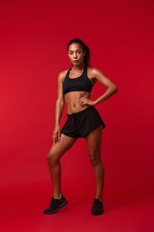 Immagine di una giovane e bella donna africana di sport fitness in posa isolata sopra il muro rosso.