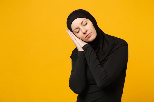 L'immagine di bella giovane donna musulmana araba in vestiti neri di hijab dorme con le mani piegate sotto la guancia isolata sulla parete gialla. concetto di stile di vita dell'islam religioso delle persone mock up copy space