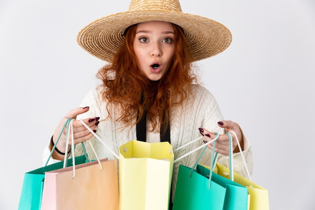 Immagine di una bella giovane rossa emotiva eccitata ragazza carina in posa isolata sopra il fondo bianco della parete che tiene i sacchetti della spesa.