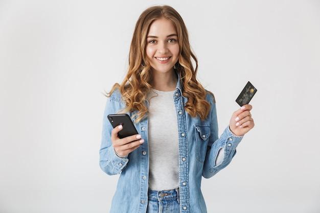 Immagine di una bella giovane donna graziosa eccitata in posa isolata sul muro bianco utilizzando la carta di credito in possesso di telefono cellulare.