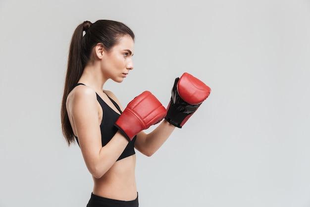 L'immagine di un bellissimo giovane pugile sportivo fitness donna isolato sul muro grigio fa esercizi con i guanti.