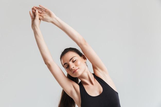 L'immagine di una bella giovane donna sportiva fitness fa esercizi isolati sul muro grigio.