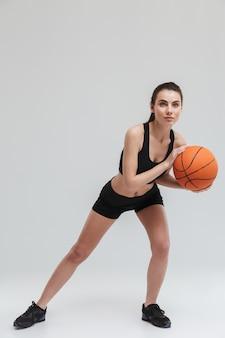 Immagine di una bella giovane donna sportiva fitness giocatore fare esercizi giocare a basket isolato sul muro grigio.
