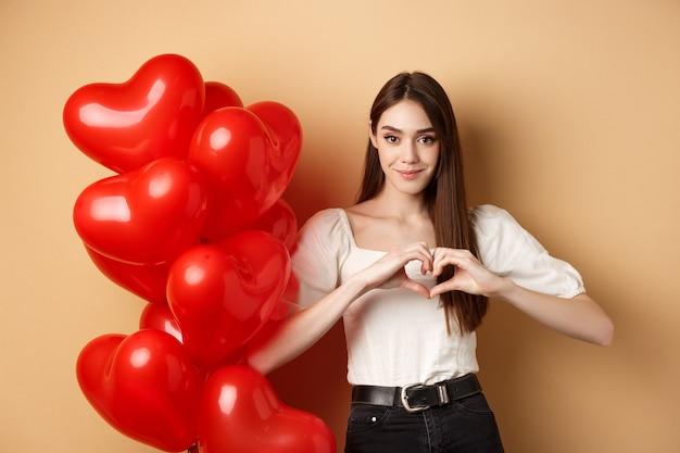 Immagine di bella giovane donna sorridente e mostrando il gesto del cuore