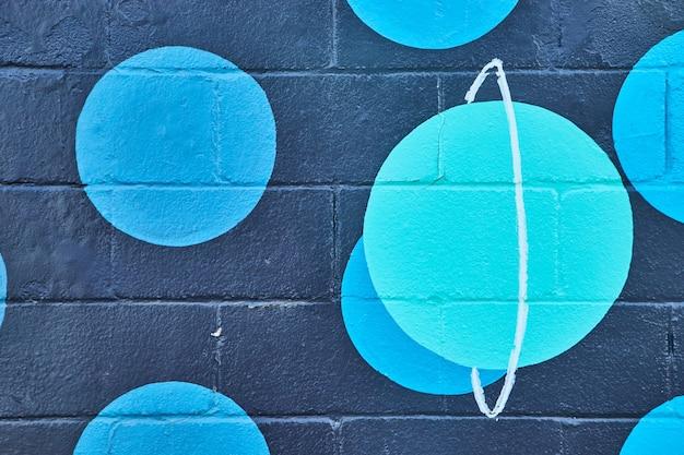 Immagine del muro dipinto di cemento nero con macchie blu e pianeta verde acqua