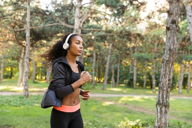 Immagine di una donna bruna 20s che indossa una tuta nera che si allena mentre corre attraverso il parco verde