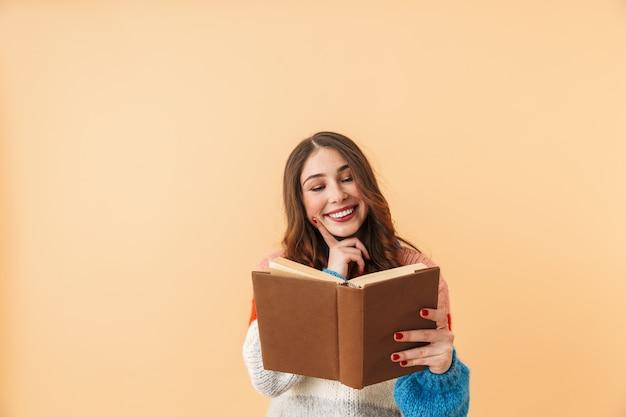 Immagine di 20s donna bruna con i capelli lunghi sorridente e leggere il libro, in piedi isolato