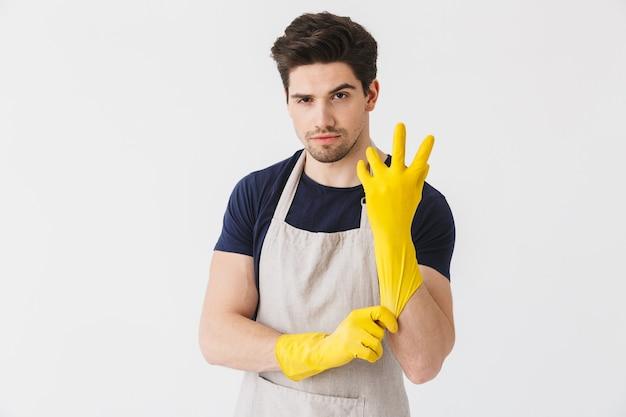 Immagine di un giovane brunetta che indossa guanti di gomma gialli per la protezione delle mani mentre pulisce la casa isolata su bianco
