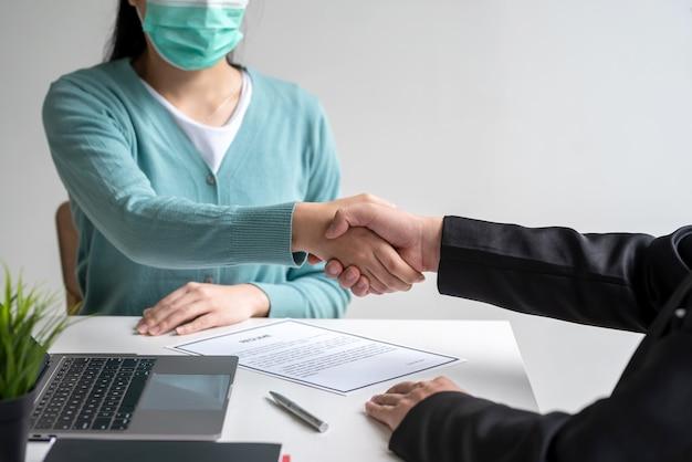Immagine di uomini d'affari che si stringono la mano accordo di lavoro in ufficio indossare una maschera per prevenire i germi.