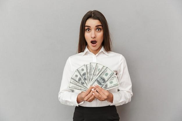 Immagine di donna d'affari con lunghi capelli castani in abbigliamento formale che tiene un sacco di banconote in dollari con la bocca aperta, isolato sopra il muro grigio