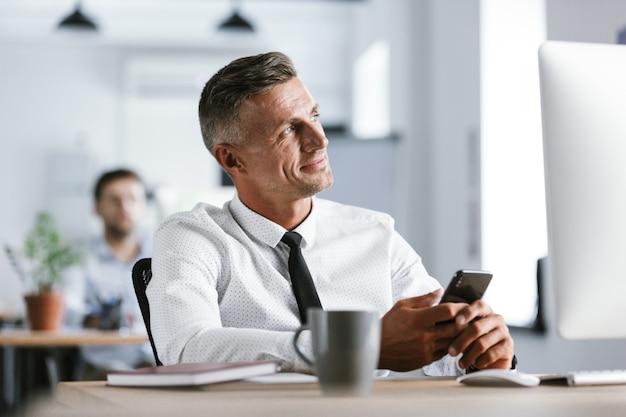 Immagine di uomo d'affari di 30 anni che indossa una camicia bianca e cravatta seduto alla scrivania in ufficio dal computer e tenendo lo smartphone