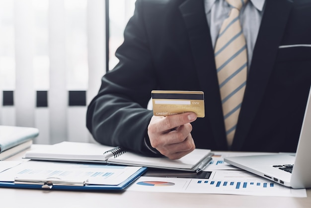 Immagine di una mano d'affari che tiene una carta di credito per lo shopping online utilizzando un grafico portatile posizionato in ufficio.