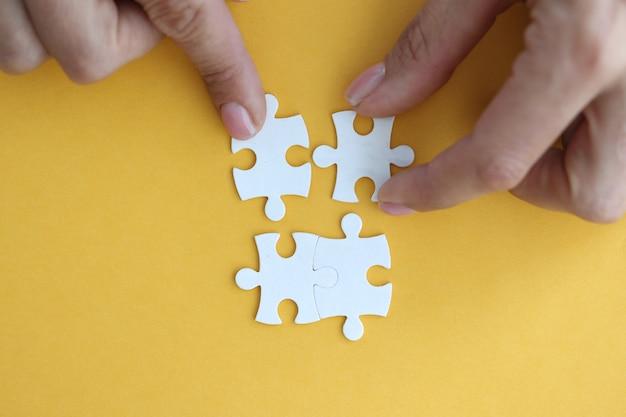 Immagine di una donna d'affari che collega gli elementi del concetto di puzzle bianco
