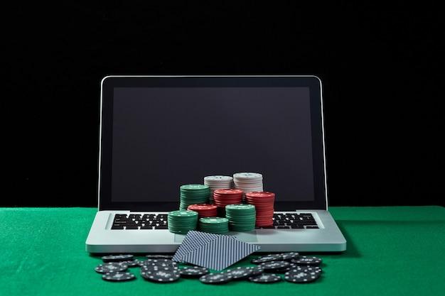 Immagine di fiches e carte del casinò su un notebook con tastiera al tavolo verde. concetto per il gioco d'azzardo online, poker, casinò virtuale.