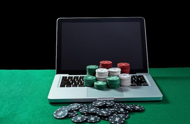 Immagine di fiches del casinò su un notebook con tastiera al tavolo verde. concetto per il gioco d'azzardo online, poker, casinò virtuale.