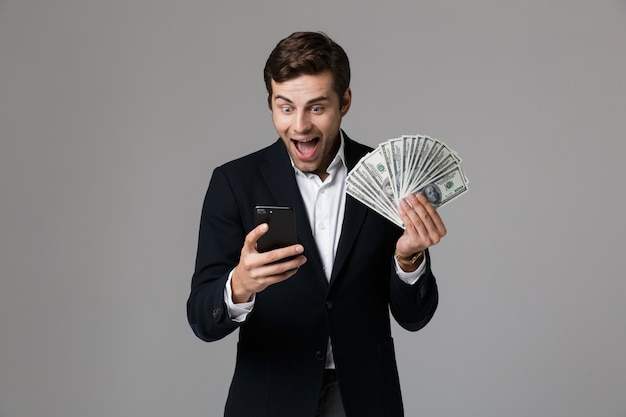 Immagine dell'uomo d'affari caucasico 30s in vestito che tiene fan di soldi e smartphone, isolato sopra il muro grigio