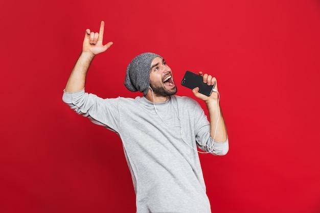 Immagine di uomo caucasico 30s cantando mentre si ascolta la musica con gli auricolari e il telefono cellulare, isolato