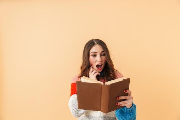 Immagine della donna caucasica 20s con i capelli lunghi sorridente e leggendo il libro, in piedi isolato