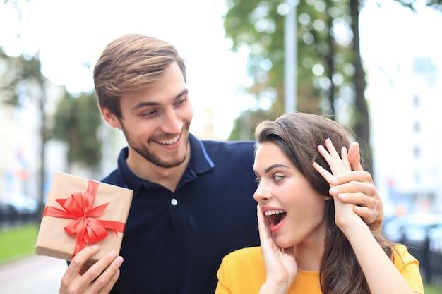 Immagine di un'affascinante coppia eccitata in abiti estivi che sorride e tiene in mano una scatola regalo all'aperto.
