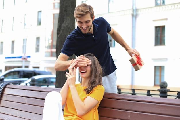 Immagine di un'affascinante coppia eccitata in abiti estivi che sorride e tiene insieme la scatola presente mentre è seduta su una panchina.