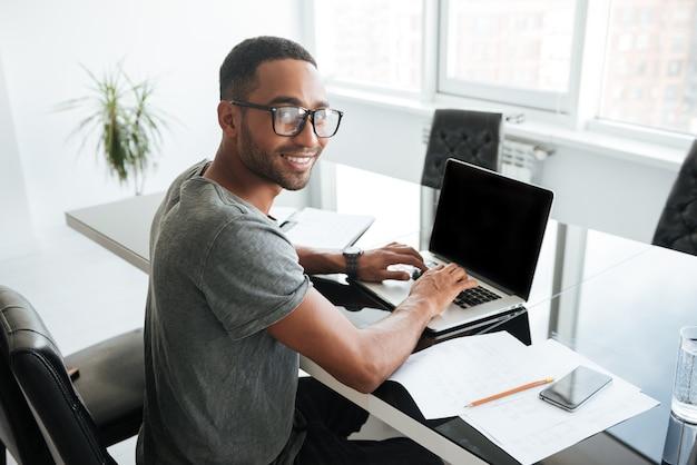 Immagine di un uomo africano allegro vestito con una t-shirt gey e con gli occhiali usando il laptop e seduto al tavolo. guardando davanti.