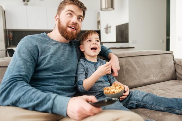 Immagine di un padre allegro che tiene il telecomando mentre guarda la tv con il suo piccolo figlio carino che tiene in mano dei popcorn.