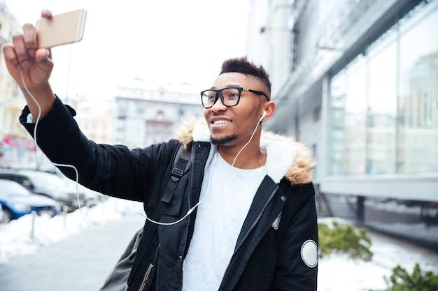 Immagine di un uomo allegro che tiene il cellulare in mano e fa un selfie mentre ascolta musica all'aperto.
